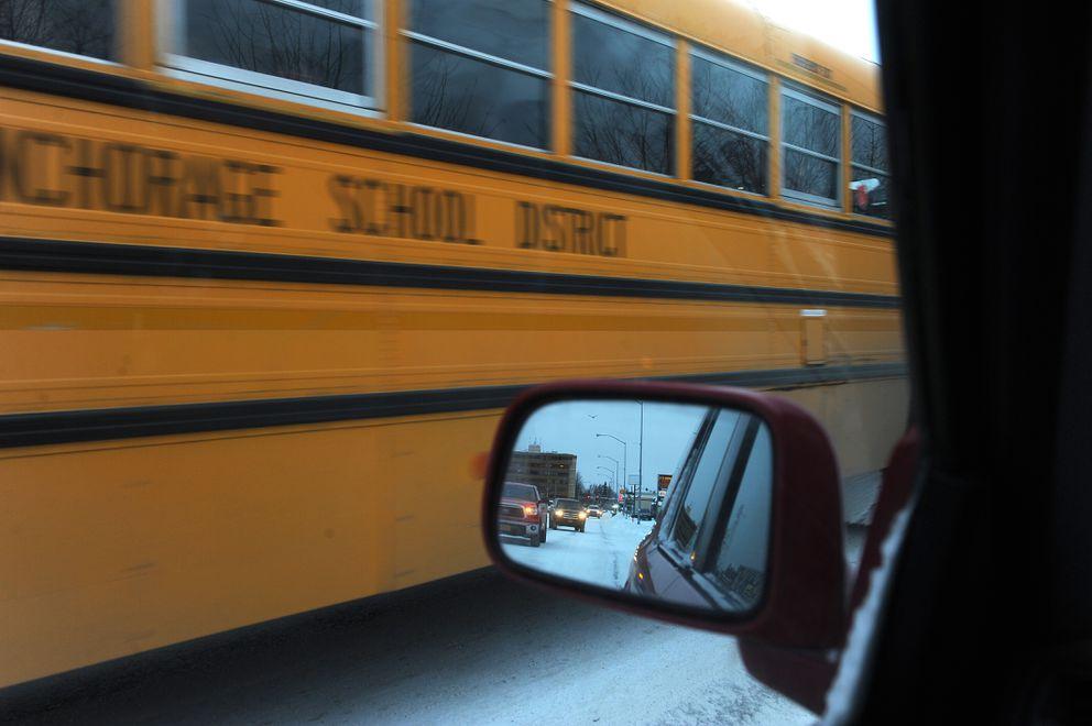 An Anchorage School District school bus travels down Spenard Road in traffic in Anchorage, Alaska, on Friday, December 2, 2016. (Bob Hallinen / ADN)
