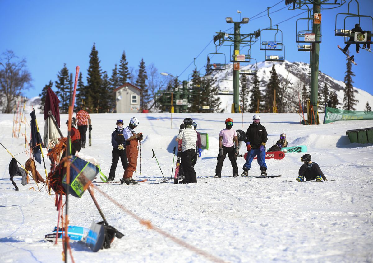 People shed layers of clothing and wait to ride a ramp in the terrain park at Hilltop Ski Area in Anchorage on a sunny Friday, April 16, 2021. (Emily Mesner / ADN)