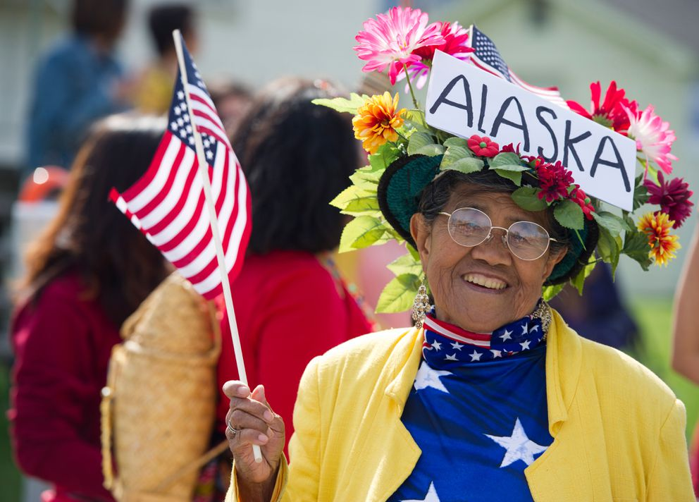 Gabriela Domanas walks with other Filipino community members in the Independence Day parade. Thousands gathered in downtown Anchorage for the Independence Day parade on 9th and 10th Avenues on Friday, July 4, 2014. A festival on the Delaney Park Strip continued through the afternoon with live music, food and games. (Marc Lester / Anchorage Daily News)