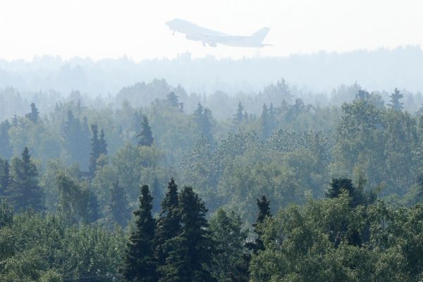 A Boeing 747 takes off from the airport as smoke from the 92,657 acres, or about 144 square mile Swan Lake wildfire on the Kenai Peninsula has settled in Anchorage reducing the visibly and lowering the air quality to an
