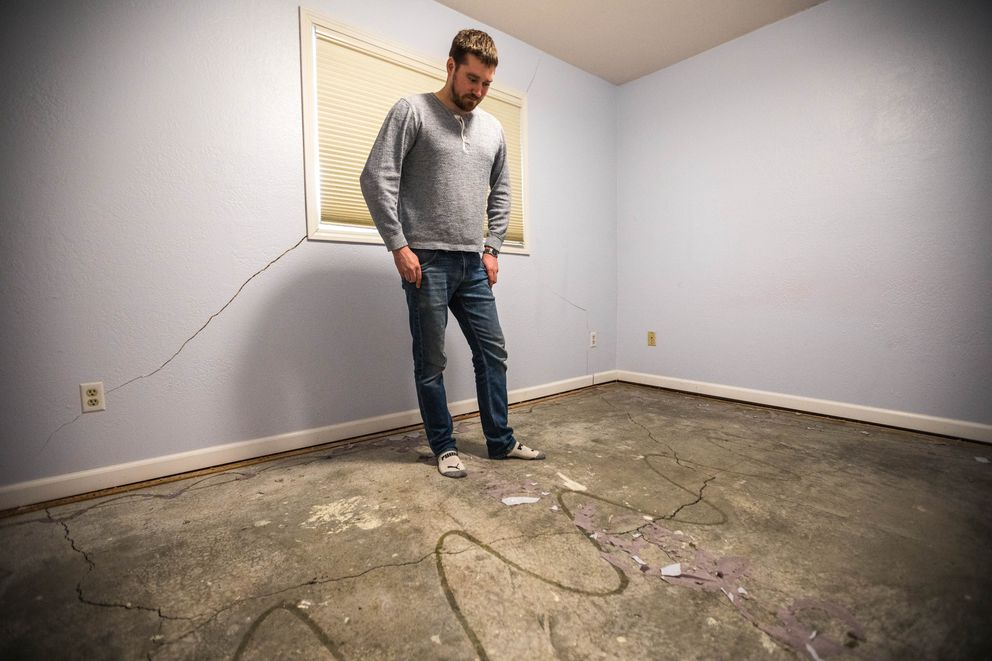 Ryan Manzek pulled up carpet in the basement of his Sand Lake home to find substantial settling of his foundation after the Nov. 30 earthquake. (Loren Holmes / ADN)
