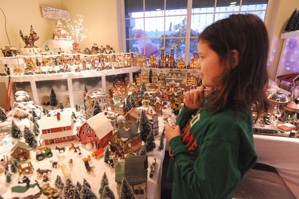 Gracie Baer considers what still needs work in the Christmas village she works on with her dad. (Anne Raup / ADN)