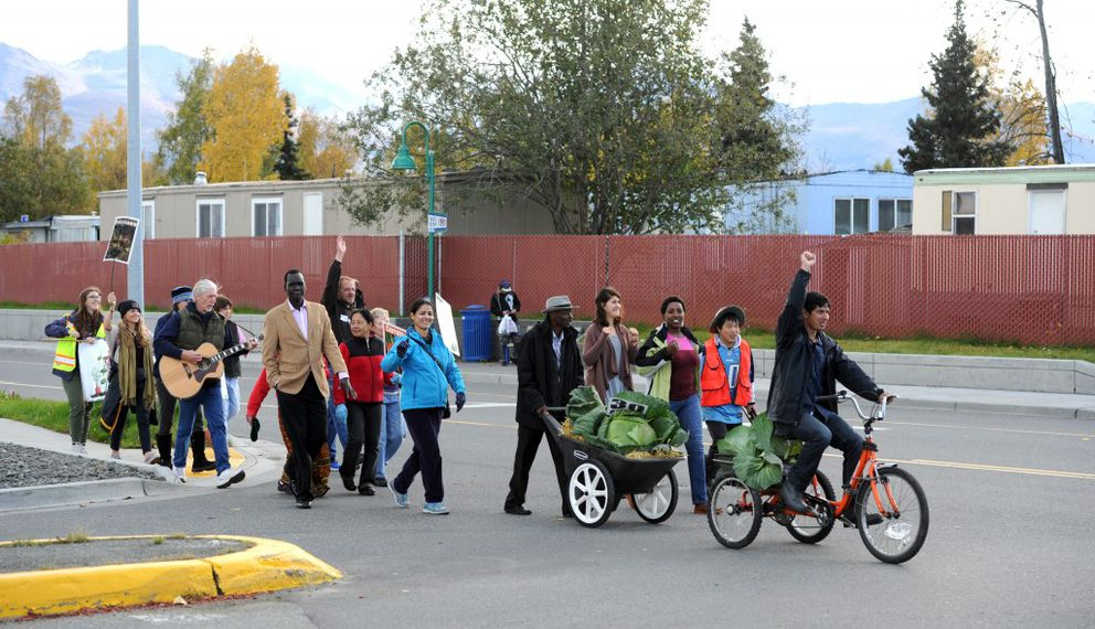 Refugee gardeners with Fresh International Gardens parade down Penland Parkway and salute colleagues as they approach their stand at the Northway Mall Wednesday Market. (Erik Hill / Alaska Dispatch News)