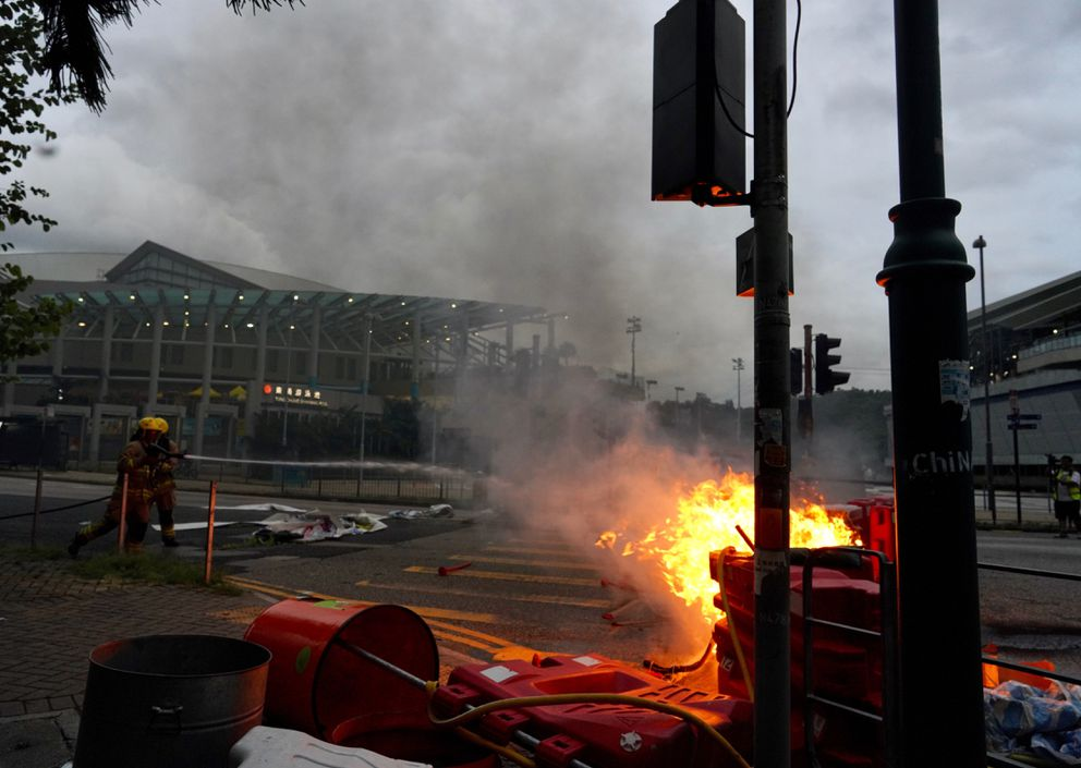 Firemen try to douse fire after protesters set fire to barricades and vandalized signages at Tung Chung near airport in Hong Kong, Sunday, Sept.1, 2019. Train service to Hong Kong's airport was suspended Sunday as pro-democracy demonstrators gathered there, while protesters outside the British Consulate called on London to grant citizenship to people born in the former colony before its return to China. (AP Photo/Vincent Yu)
