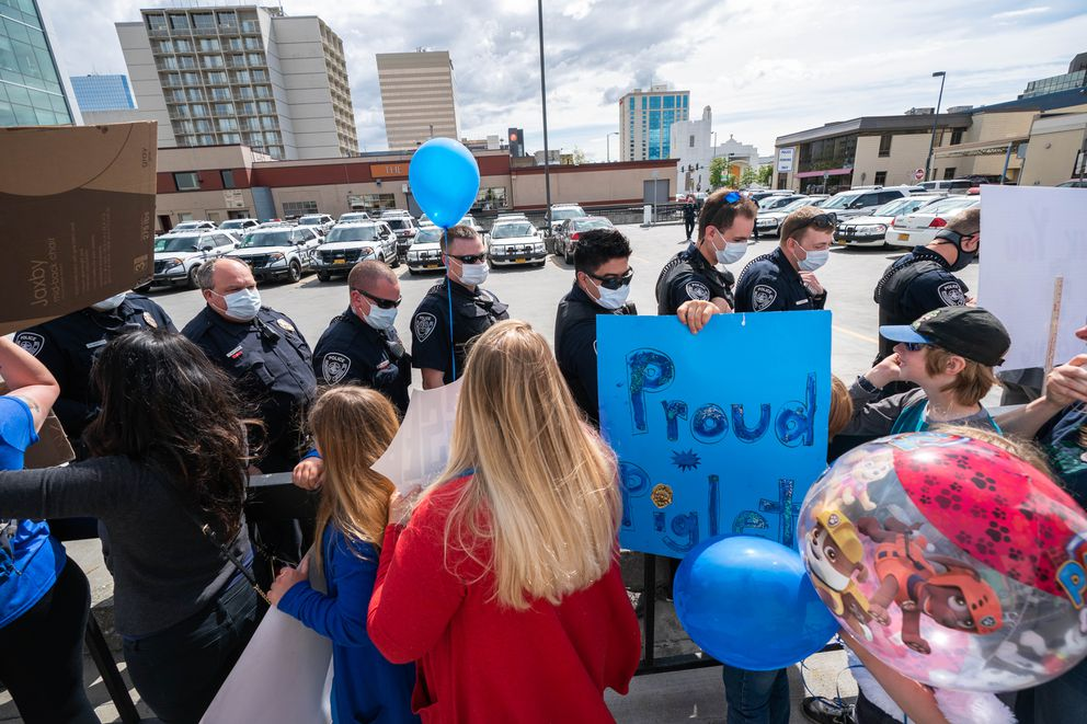 Anchorage police officers walk past supporters outside police headquarters on Thursday, June 18, 2020 in downtown Anchorage. According to rally organizer Judy Eledge, over 100 people gathered to show support for the local law enforcement agency. (Loren Holmes / ADN)