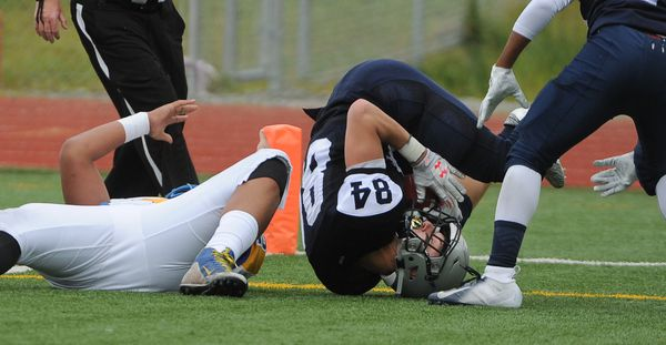 Anthony Fruean, of Barrow High, lies on the field as Mason Piper of Eagle River rolls over after making the interception in the end zone at Eagle River High on Thursday, August 16, 2018. Piper stopped the Barrow drive on the last play of the first half. Eagle River won 50-3. (Bob Hallinen / ADN)