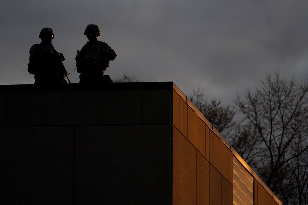 Law enforcement officers stand on top of the Brooklyn Center Police Department during a protest over the fatal shooting of Daunte Wright by a police officer during a traffic stop, Saturday, April 17, 2021, in Brooklyn Center, Minn. (AP Photo/Julio Cortez)