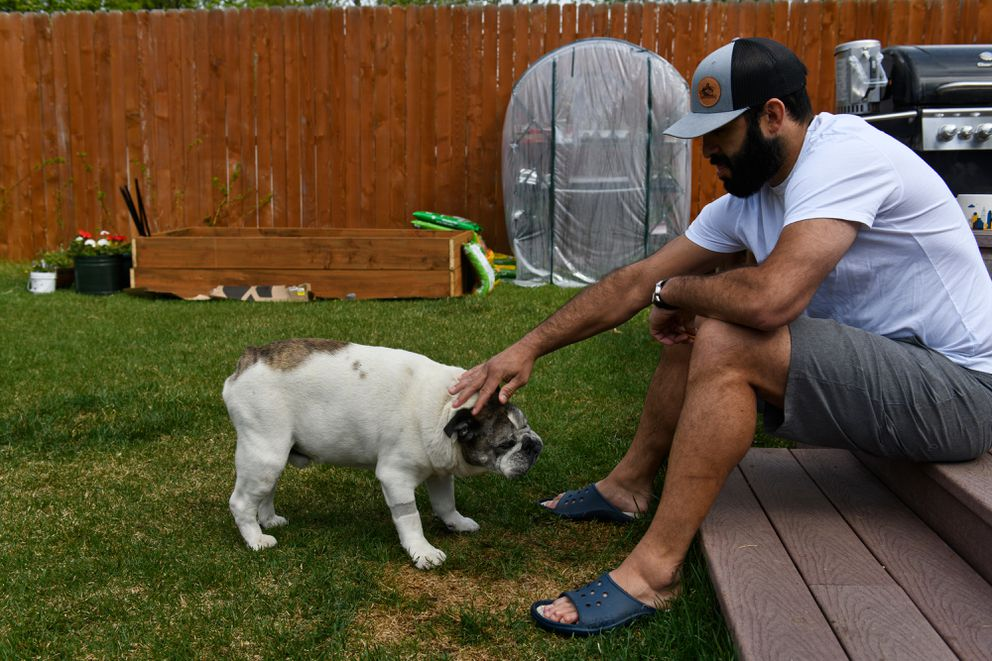 Former NHL player Scott Gomez pets his dog, Bacon, in his back yard. (Marc Lester / ADN)
