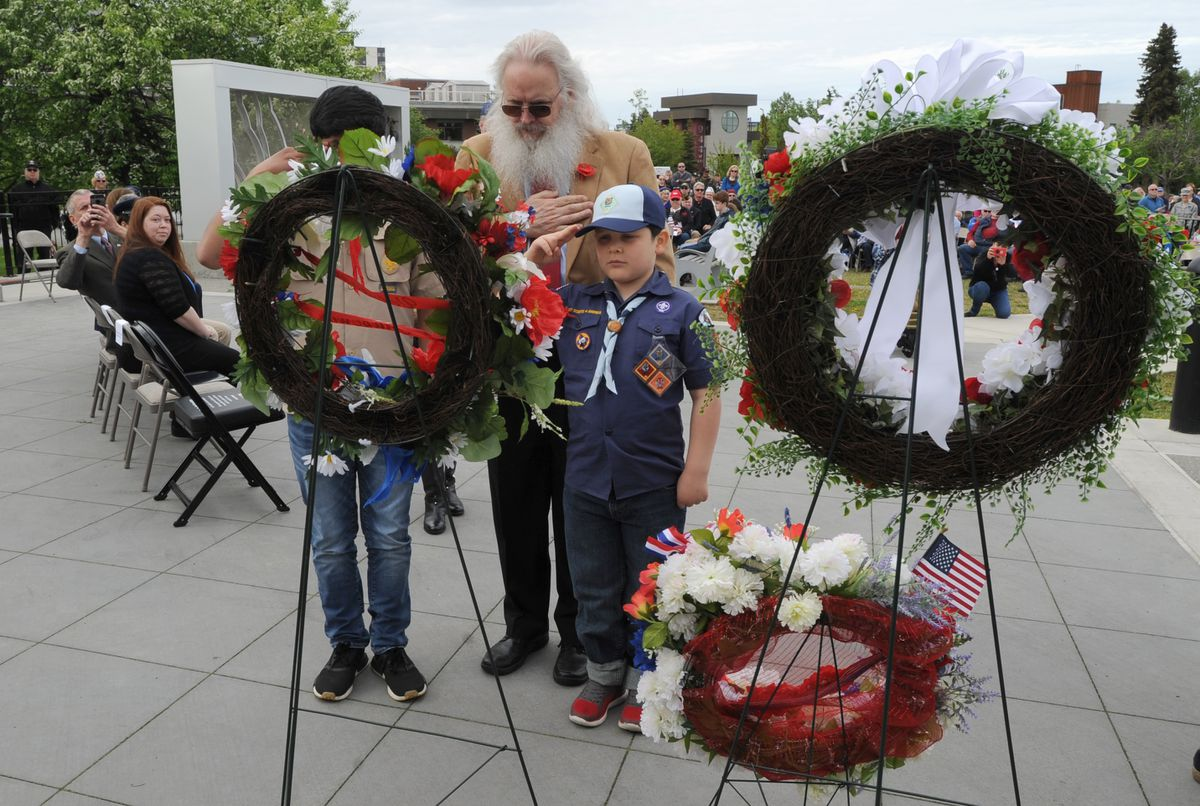 Michael Haller (middle with beard) and his grandsons Edward Haller (behind the wreath), and Rolan Haller present a wreath during the Memorial Day ceremony on the Park Strip Monday, May 27, 2019. (Anne Raup / ADN)