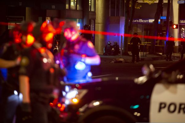 Police gather near where a person was shot Saturday night, Aug. 29, 2020, in Portland, Ore. Fights broke out in downtown Portland as a large caravan of supporters of President Donald Trump drove through the city, clashing with counter-protesters. (Dave Killen/The Oregonian via AP)