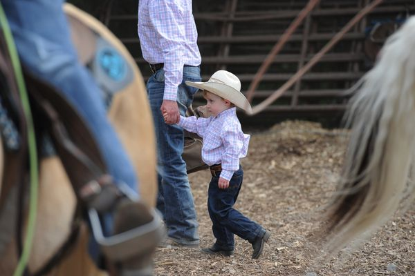 Weston Lacey, 3, walks with his father Lance Lacey as they prepare to compete in the Mutton Busting and Chute Dogging events during the Rodeo Alaska Father's Day Rodeo at the William Clark Chamberlin Equestrian Center in Anchorage on Sunday, June 18, 2017. (Bill Roth / Alaska Dispatch News)