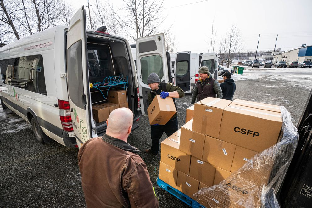 Salmon Berry Tours guide Brendan Thompson, second from left, loads boxes of food into a van at the Food Bank of Alaska on Friday. (Loren Holmes / ADN)