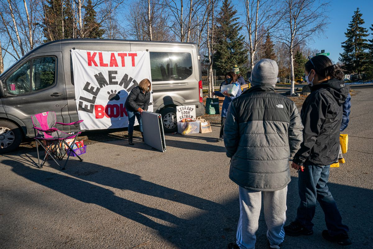 Klatt Elementary School librarian Genevieve Stephens sets up a mobile book delivery station on Wednesday, Oct. 21, 2020 at the Dimond Estates mobile home park. About 75% of the students at Klatt live in the park, which is over 3 miles from the school. (Loren Holmes / ADN)