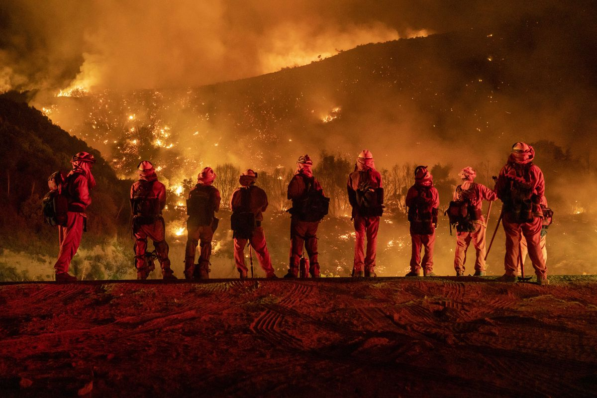Inmate firefighters watch as the El Dorado Fire burns a hillside near homes in Mountain Home Village, Calif., inside the San Bernardino National Forest on Sept. 9, 2020. (Photo by Kyle Grillot for The Washington Post)