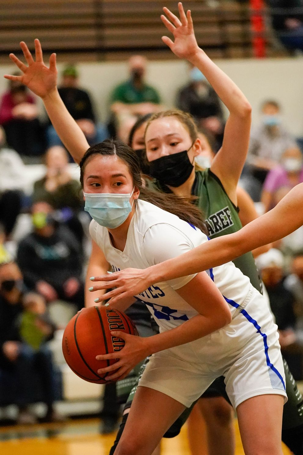 Newhalen's Johnna Nanalook looks for an opening between Shishmaref defenders Autumn Barr, behind, and Timary Stenek. (Loren Holmes / ADN)