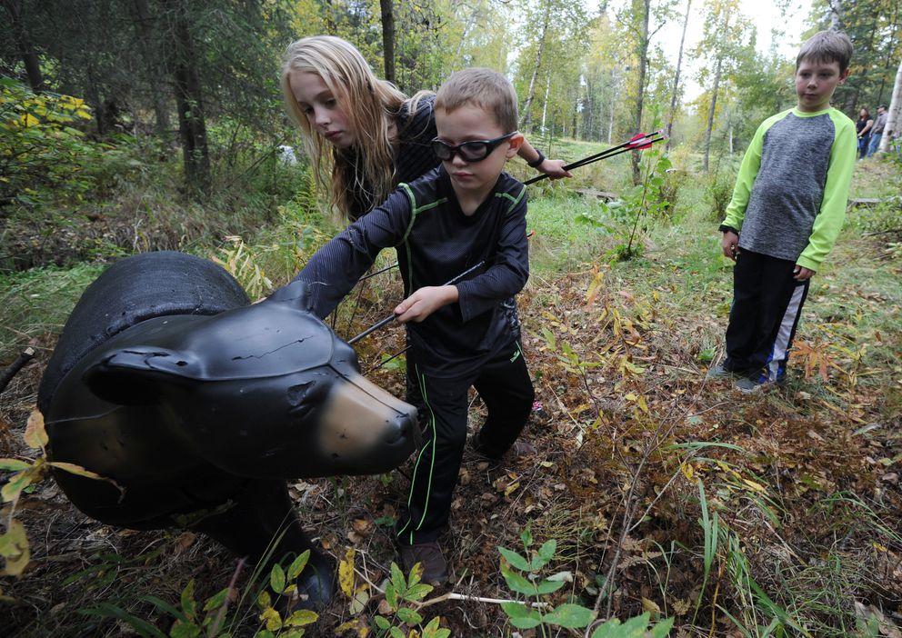 From left, Madison Davis, 9, Hunter Davis, 7, and Cole Stoddard, 9, remove arrows from a bear 3D archery target on Monday, Sept. 12, 2016. (Bill Roth / Alaska Dispatch News)