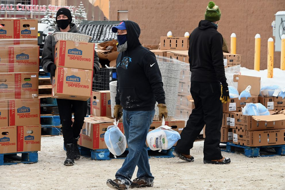 Volunteers, from left, Nathan Harmston, Johnny Provost and Mark Iverson helped load groceries and frozen turkeys into a vehicle during the Thanksgiving Blessing food distribution drive-thru at the old Sam's Club at Tikahtnu Commons in Muldoon on Monday, Nov. 23, 2020. (Bill Roth / ADN)