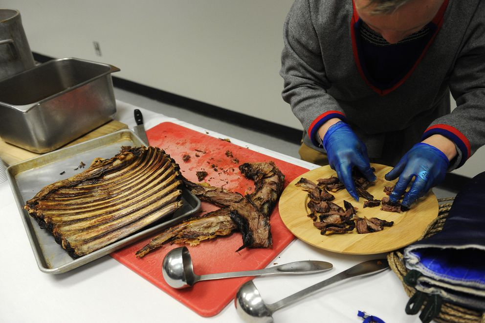 Nils Pendik of Norway cuts up reindeer ribs for samples at the Perspectives in Circumpolar Reindeer Production session during the Arctic Council on Wednesday. (Bob Hallinen / Alaska Dispatch News)