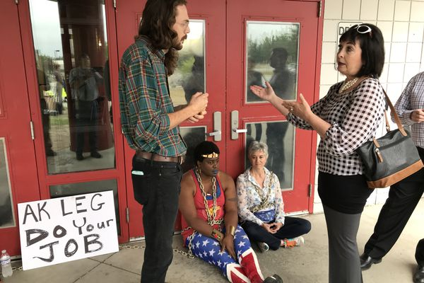 Sen. Shelley Hughes, R-Palmer, right, talks to protestors blocking main entrance to Wasilla Middle School on Wednesday morning, July 10, 2019, before a special session. (Bill Roth / ADN)