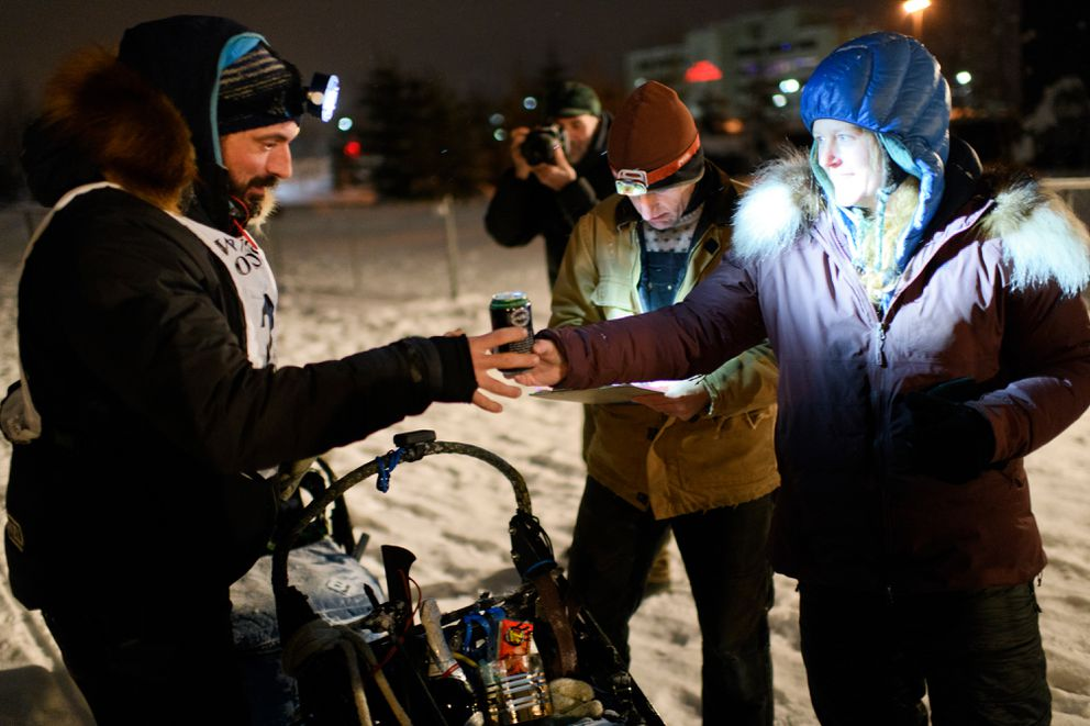 Paige Drobny, right, hands her husband, Cody Strathe, a beer after he reached the finish line of the Yukon Quest International Sled Dog Race on Feb. 13. Drobny finished the race in sixth place, and Strathe finished in 12th. (Marc Lester / ADN)