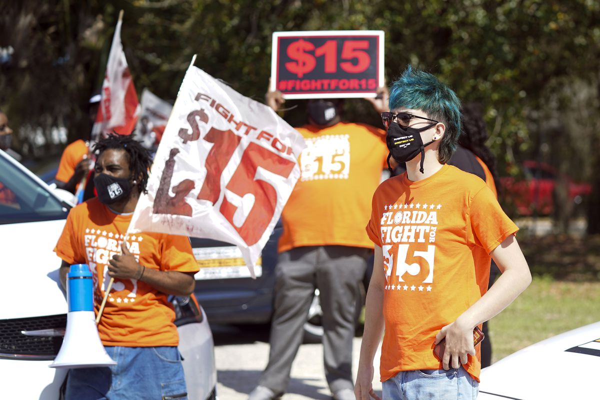 Cristian Cardona, right, an employee at a McDonald's, attends a rally for a $15 an hour minimum wage Tuesday, Feb. 16, 2021, in Orlando, Fla. (AP Photo/John Raoux)