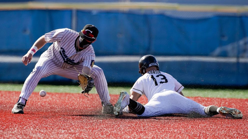 South's Kellen Curtis slides safely into second base before Chugiak's Zach Cole catches the ball Saturday at Bartlett High. (Loren Holmes / ADN)