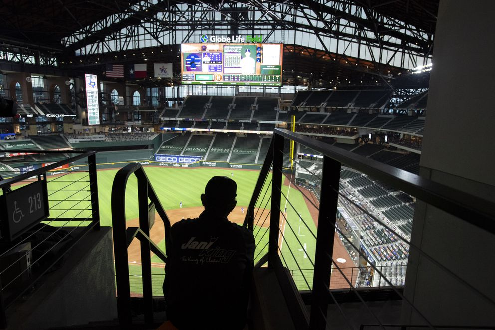 Globe Life Park custodian Erazmo Gonzalez watches from the upper deck during an opening day baseball game between the Texas Rangers and the Colorado Rockies, Friday, July 24, 2020, in Arlington, Texas. (AP Photo/Jeffrey McWhorter)