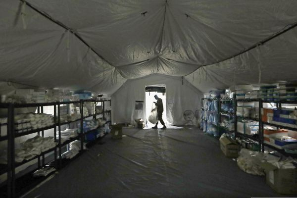 FILE - In this March 31, 2020, file photo a U.S. Army soldier walks inside a mobile surgical unit being set up by soldiers from Fort Carson, Col., and Joint Base Lewis-McChord (JBLM) as part of a field hospital inside CenturyLink Field Event Center, in Seattle. As of last week, the Army had already exceeded its retention goal of 50,000 soldiers for the fiscal year ending in September, re-enlisting more than 52,000 so far. (AP Photo/Elaine Thompson, File)