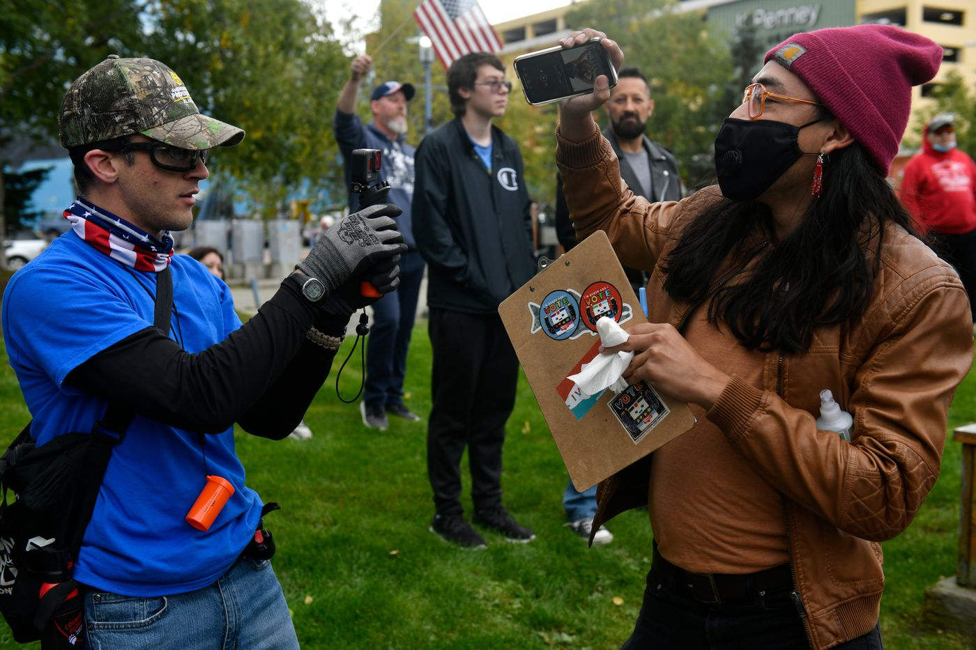 A man dancing and distributing absentee ballot applications, right, is recorded by another man during the March on Alaska event. (Marc Lester / ADN)
