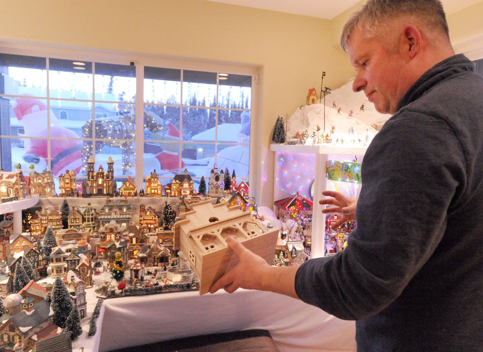Nate Baer holds an in-progress building that will one day be a model of Chilkoot Charlie's bar. (Anne Raup / ADN)