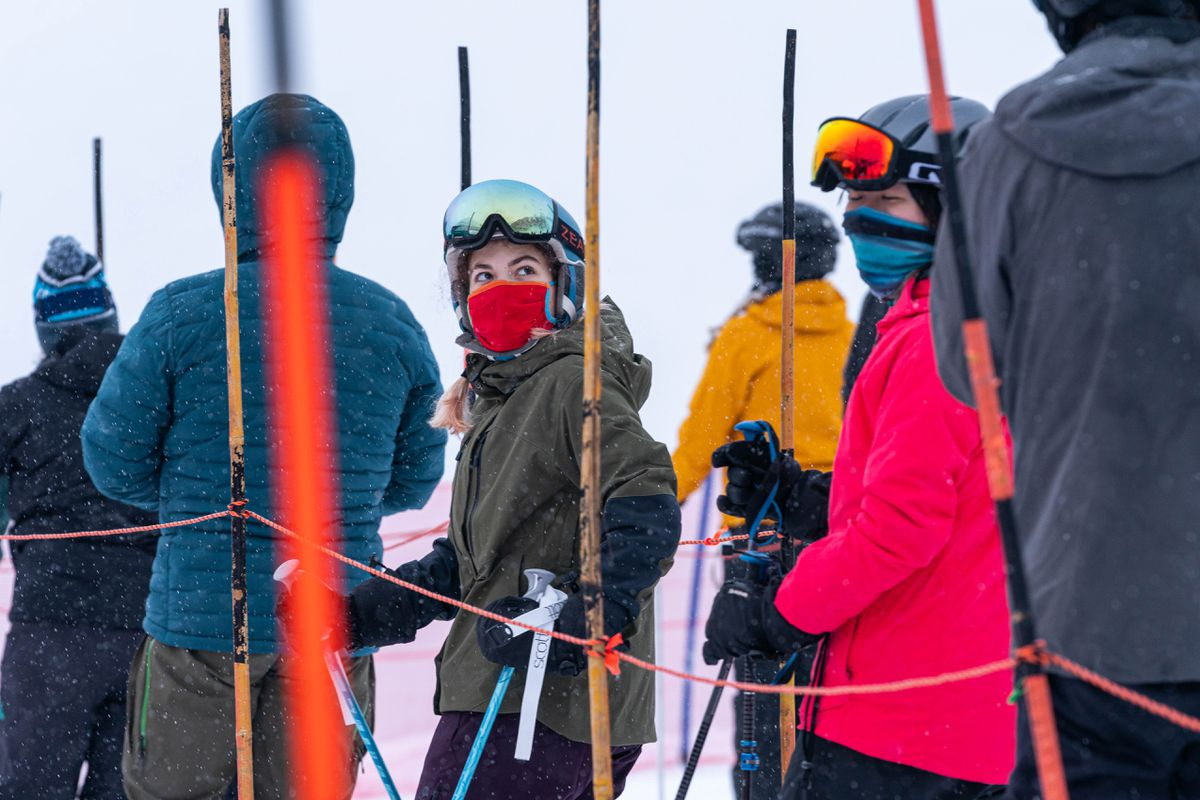 Skiers wear masks while waiting in a lift line at Alyeska Resort on opening day Friday. The resort has a number of new policies designed to limit the spread of COVID-19, including increased physical distancing and mandatory mask policies. (Loren Holmes / ADN)