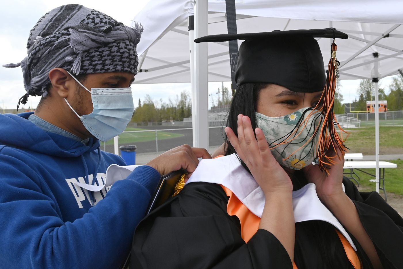 West High School senior Nicole Cedeno-Huff gets help from her brother George Cedeno-Huff as she prepares to have a photo taken in her graduation robe on Monday, May 18, 2020. (Bill Roth / ADN)