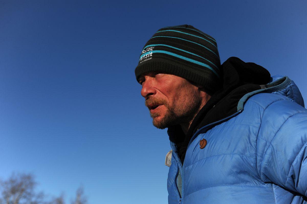 Jason Mackey comes out of the Huslia checkpoint building into the warm sunshine during the Iditarod Trail Sled Dog Race on Friday. (Bob Hallinen / Alaska Dispatch News)