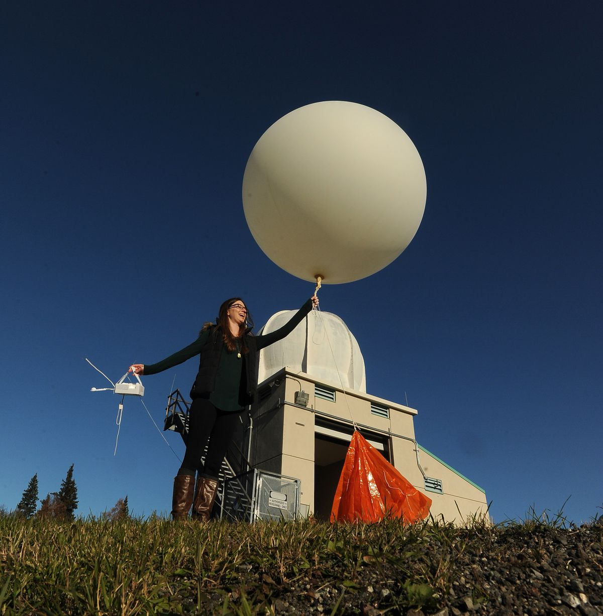 Rebecca Duel, meteorologist at the Anchorage Forecast Office of the National Weather Service, launches a weather balloon at the center in Anchorage on Friday, Oct. 7, 2016. (Bob Hallinen / Alaska Dispatch News)