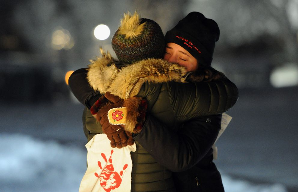 Charlene Apok, left, and Ruth Miller embrace during a vigil at Delaney Park Strip in Anchorage on Wednesday evening, Jan. 15, 2020, for Kristen Huntington who's death in Fairbanks last week is being investigated as a homicide. (Bill Roth / ADN)