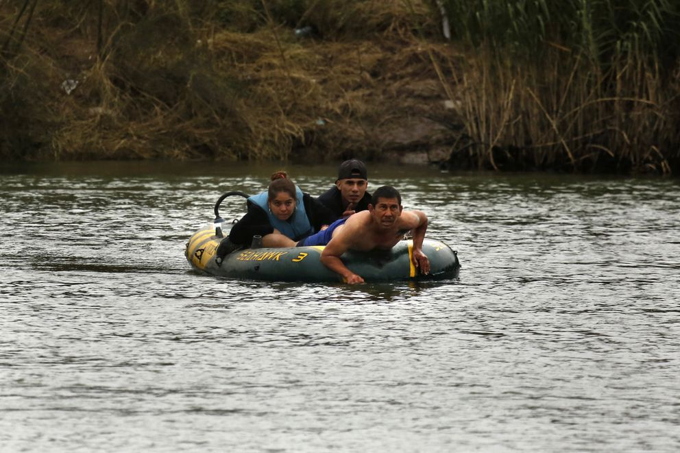 A smuggler tries to bring two people from Miguel Aleman, Mexico, to Roma, Texas, in a small rubber raft, but the presence of U.S. Border Patrol agents deterred them and they turned back. (Carolyn Cole/Los Angeles Times/TNS)