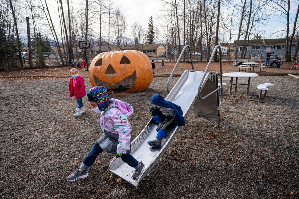 Emani Bell, left, and Abel Rice play on a slide at Carousel Child Care Center on Friday, April 30, 2021 in Anchorage. (Loren Holmes / ADN)