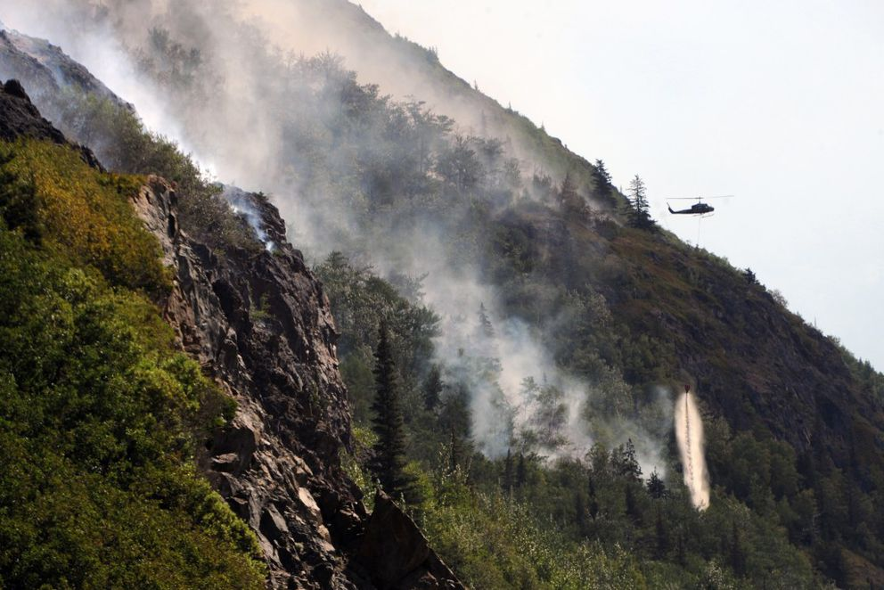 A helicopter drops water on the McHugh Creek wildfire on a slope above the Seward Highway on Tuesday afternoon, July 19, 2016, along Turnagain Arm. (Erik Hill / Alaska Dispatch News)