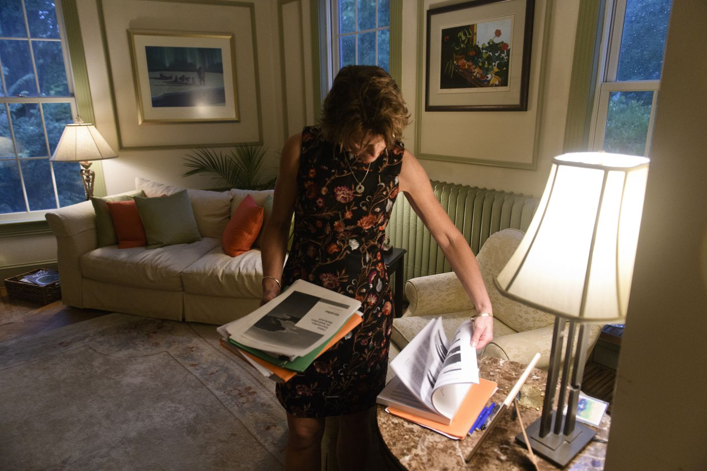 Sen. Lisa Murkowski holds a stack of her 'homework ' reading and browses another stack, which includes a copy of the Mueller Report, in her Washington living room on June 18, 2019. (Marc Lester / ADN)