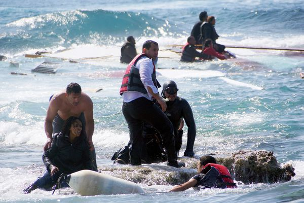 A man rescues an migrant from the Aegean sea, in the eastern island of Rhodes, Monday, April 20, 2015. Greek authorities said that at least three people have died, including a child, after a wooden boat carrying tens of migrants ran aground off the island of Rhodes. (Argiris Mantikos/Eurokinissi via AP)