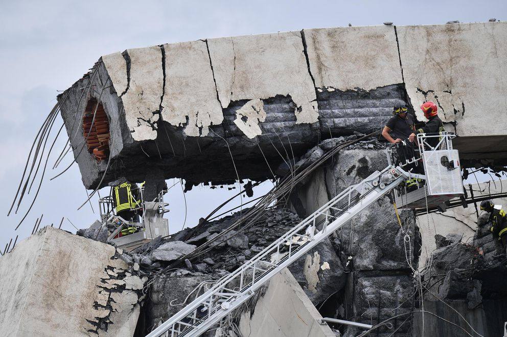 Firefighters inspect the Morandi highway bridge that collapsed in Genoa, northern Italy, Tuesday, Aug. 14, 2018. The highway bridge collapsed during a violent storm, sending vehicles plunging 45 meters (nearly 150 feet) into a heap of rubble. Authorities said at least 20 people were killed, although some people were found alive in the debris. (Luca Zennaro/ANSA via AP)