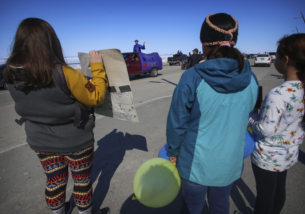 Brian Stalker waves to friends and family on Sikaagruk Shore Avenue as he passes by during the senior graduation parade in Kotzebue on Saturday, May 2, 2020. (Photo by Emily Mesner)