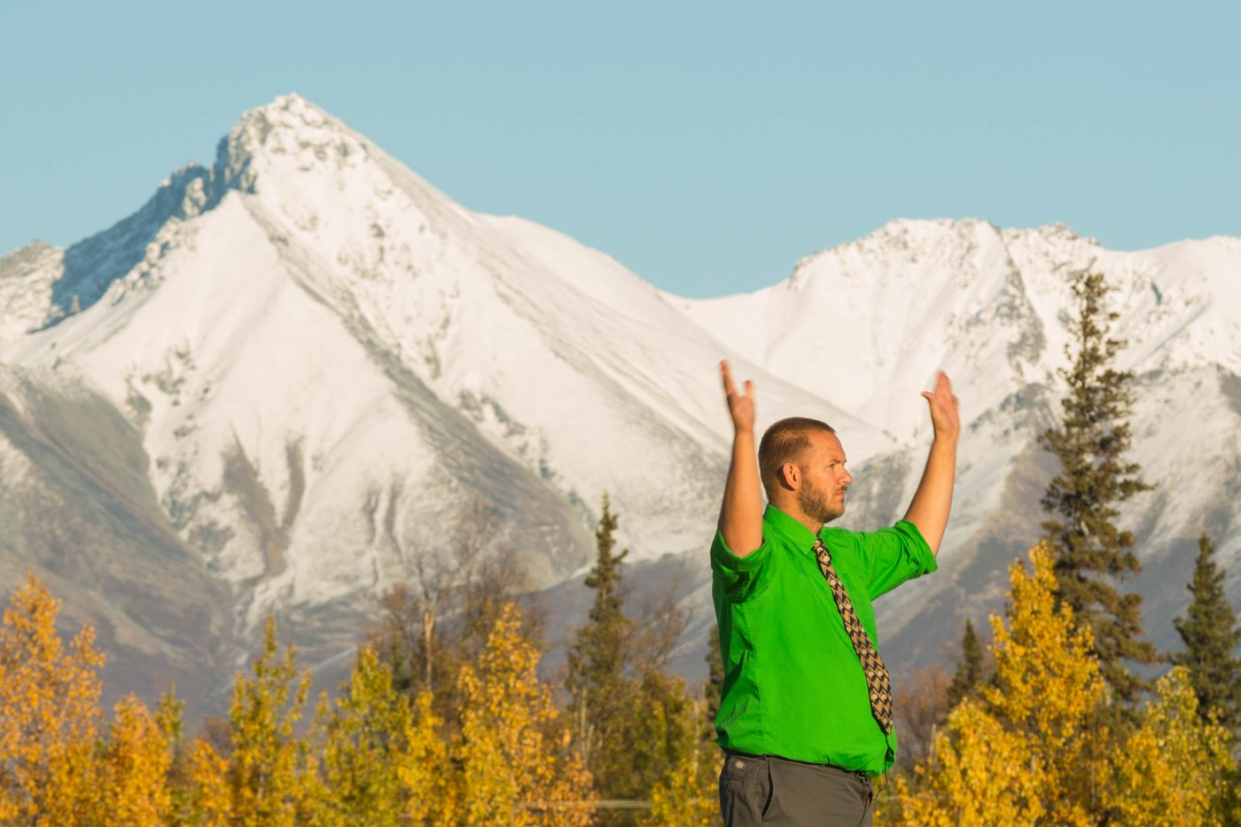With Matanuska Peak behind, Colony High School band director Jamin Burton conducts the marching band during a performance on Thursday, September 24, 2015. His group is the only high school marching band in Alaska.