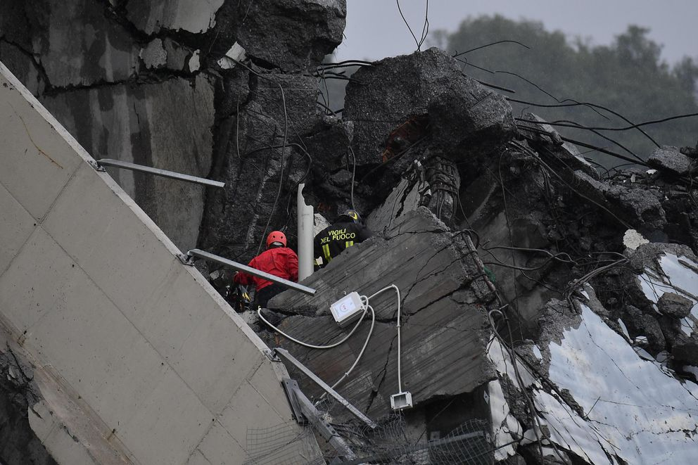 Rescuers among the rubble of the Morandi highway bridge that collapsed in Genoa, northern Italy, Tuesday, Aug. 14, 2018. A large section of the bridge collapsed over an industrial area in the Italian city of Genova during a sudden and violent storm, leaving vehicles crushed in rubble below. (Luca Zennaro/ANSA via AP)