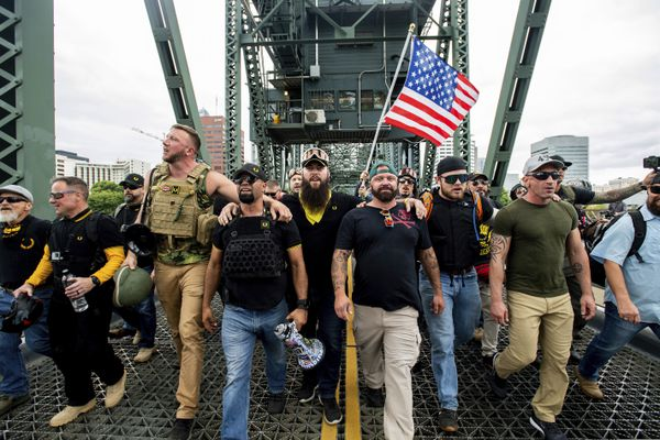 FILE - In this Aug. 17, 2019, file photo, members of the Proud Boys and other right-wing demonstrators march across the Hawthorne Bridge during a rally in Portland, Ore. The group includes organizer Joe Biggs, in green hat, and Proud Boys Chairman Enrique Tarrio, holding megaphone. At least several thousand people are expected in Portland on Saturday, Sept. 26, 2020, for a rally in support of President Donald Trump and his re-election campaign as tensions boil over nationwide following the decision not to charge officers in Louisville, Kentucky for killing Breonna Taylor. (AP Photo/Noah Berger, File)