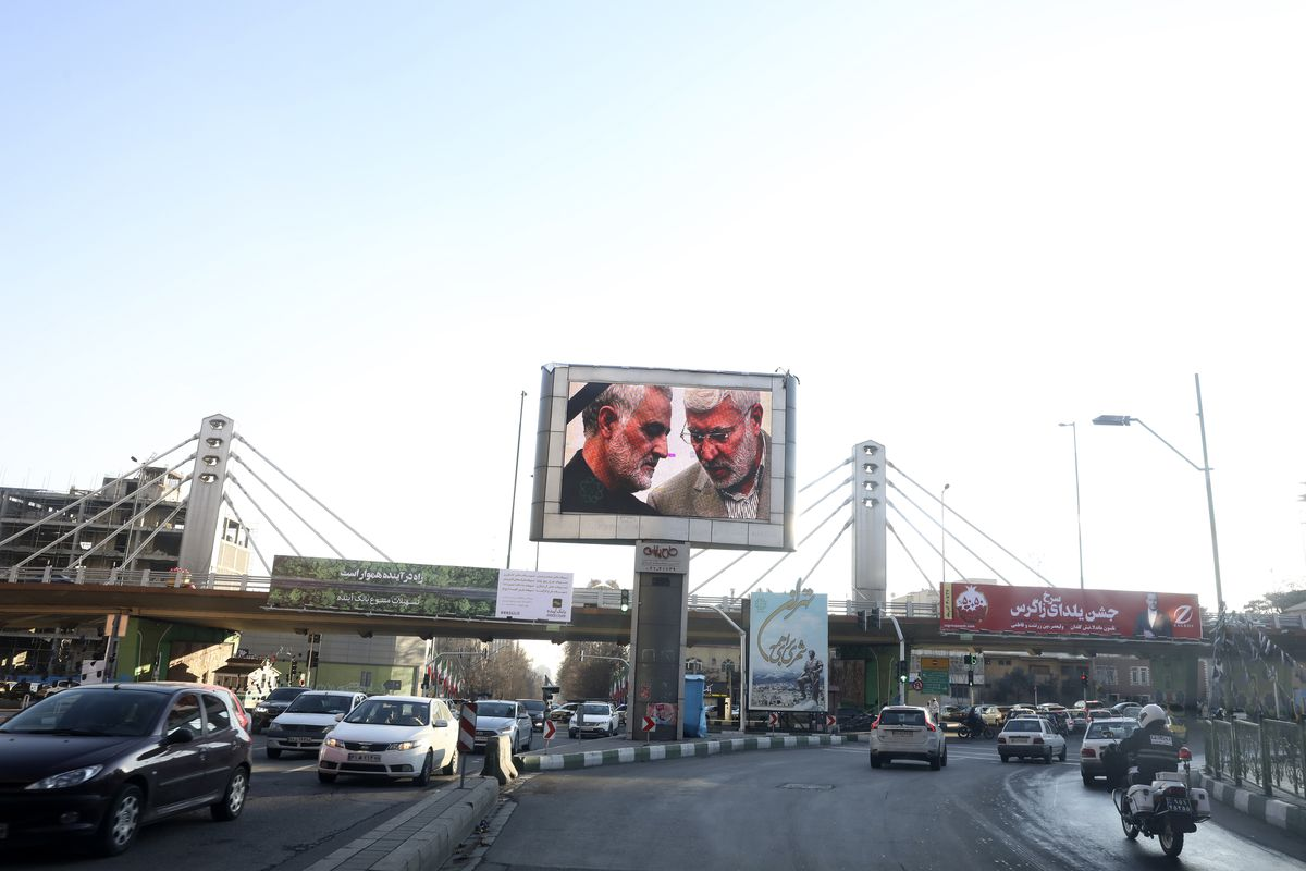 Portraits of Iranian Revolutionary Guard Gen. Qassem Soleimani, left, and Iraqi Shiite senior militia commander Abu Mahdi al-Muhandis, who were killed in Iraq in a U.S. drone attack on Friday, are shown on a screen in northern Tehran, Iran, Thursday, Jan. 9, 2020. Many Iranians say they are relieved that neither their country nor the United States appear primed right now for a more direct military confrontation that could lead to war. (AP Photo/Vahid Salemi)