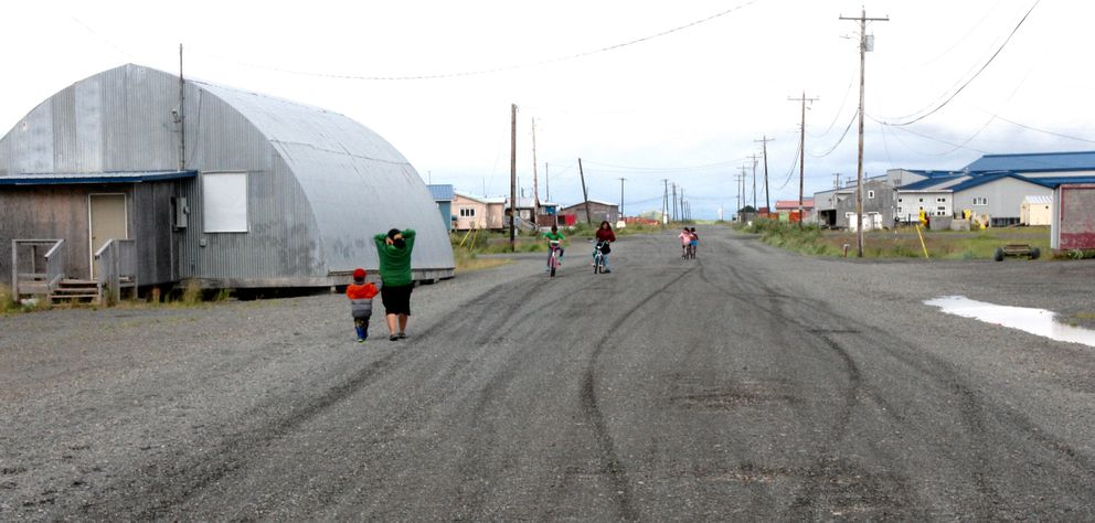 The gravel road is busy on Friday, July 22, 2016, with walkers, bikers and often four-wheelers in the Southwest Alaska village of Quinhagak. (Lisa Demer / Alaska Dispatch News)