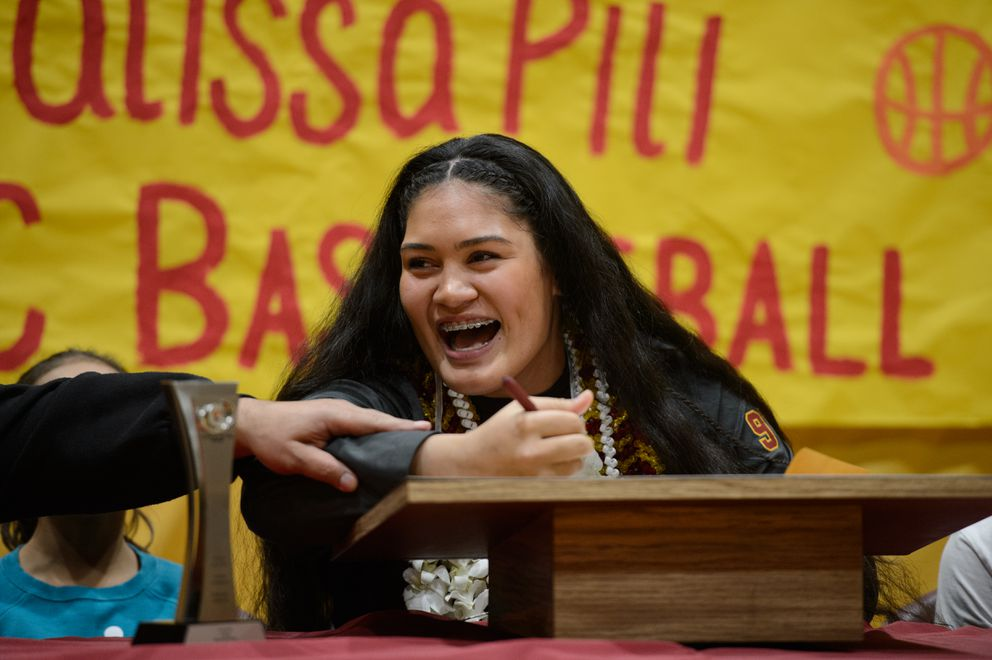 Billy Pili grabs his daughter Alissa Pili's arm and jokingly asks if anyone wants her to go to a different college just before she signs her National Letter of Intent. (Marc Lester / ADN)