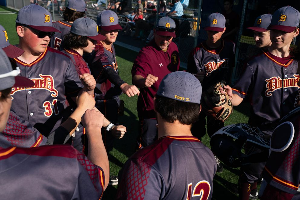 Dimond High players huddle between innings of their Friday game against Bartlett. (Loren Holmes / ADN)