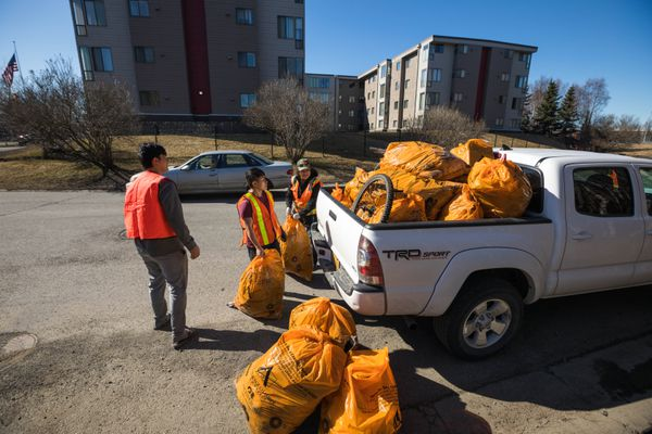 Volunteers from a Hmong group at Faith Lutheran Church deposit trash they picked up from along the Seward Highway near Tudor Road on Saturday, April 27, 2019. (Loren Holmes / ADN)